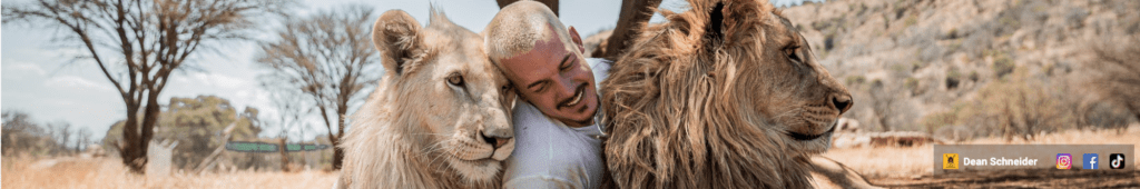 A picture of Dean Schinedar having a good time with two lions.